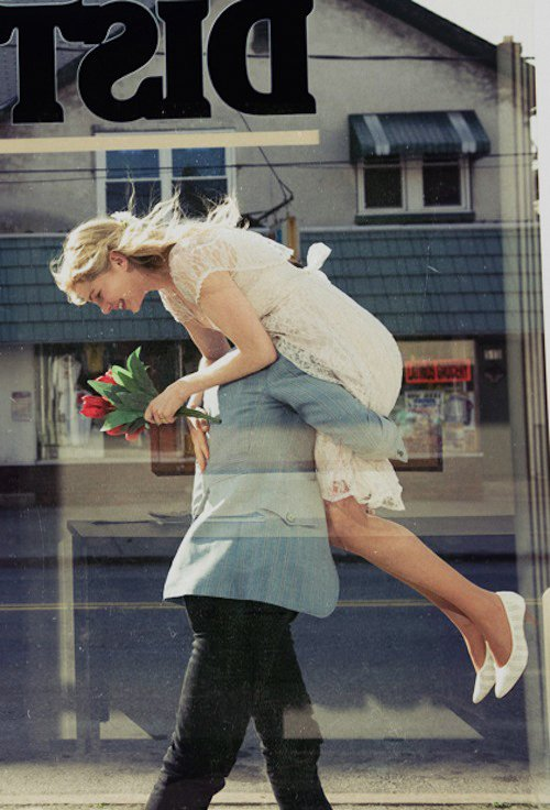 hombre cargando a una chica en los hombros en medio de la calle