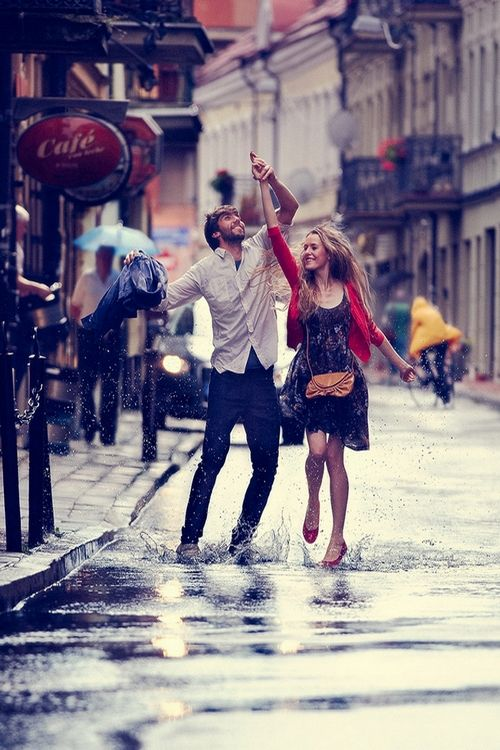 novios caminado por la calle pisando los charcos y sosteniendo una sombrilla