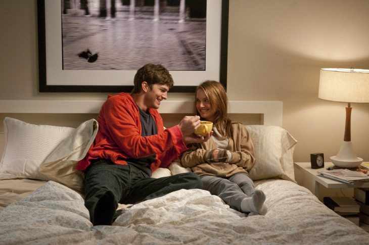 pareja de novios sentados en la cama y él dandole de comer sopa caliente en la cama