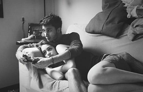 pareja recostada en un sofá jugando video juegos