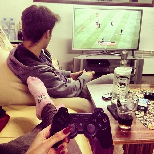 hombre sentado frente a la televisión jugando un videojuego mientras esta en una sala