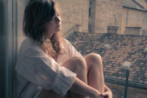 chica sentada cerca de una ventana mirando hacia la calle