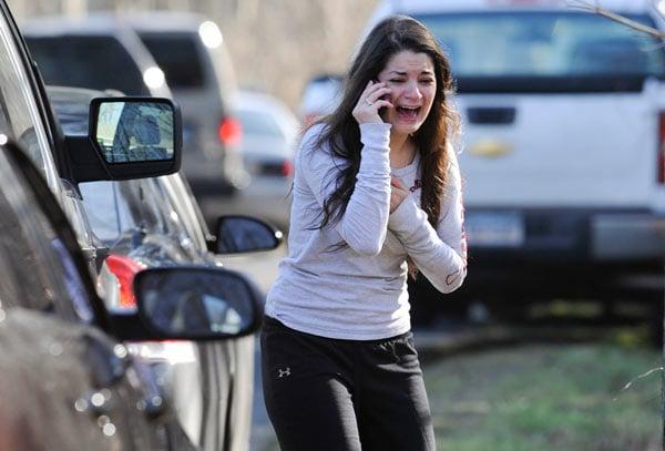 mujer parada junto a un auto llamando por celular y llorando en la calle