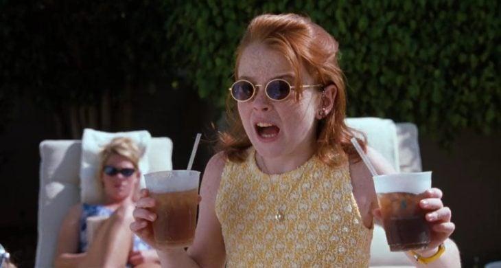 niña con lentes obscuros sosteniendo vasos con refresco