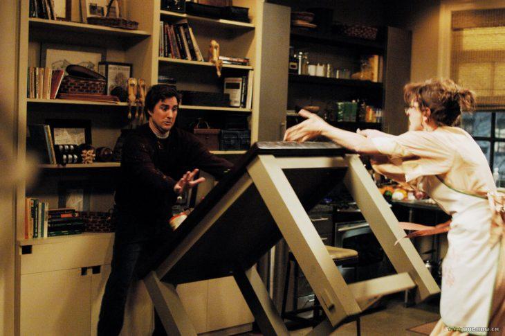 mujer aventándole una mesa a un hombre