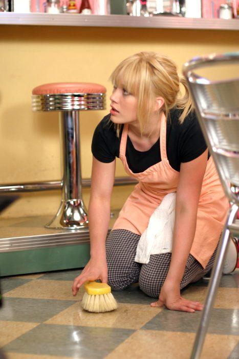 chica de rodillas tallando el suelo con un cepillo