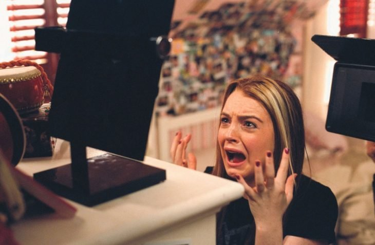 chica parada frente a un espejo gritando