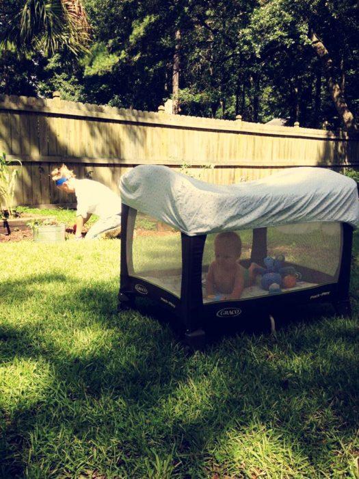 bebé en su corral cubierto con sabana