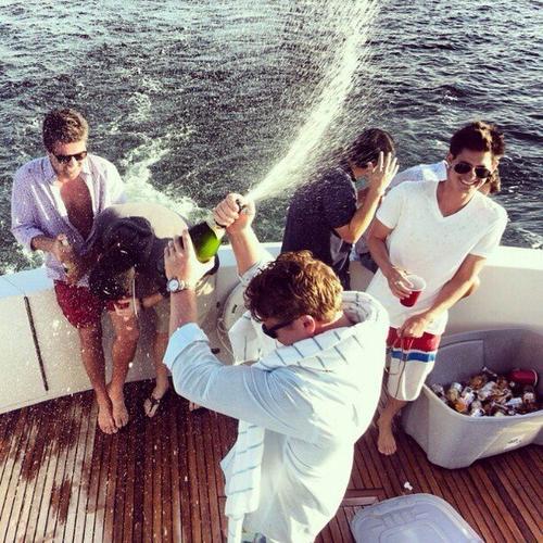 amigos en barco abriendo botella de alcohol