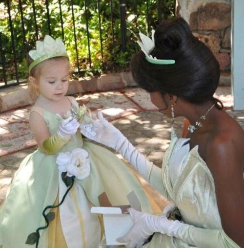 niña vestida de verde recibiendo una flor de una mujer