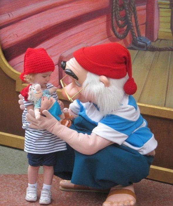 niña vestida de pinocho con juguetes en sus manos acompañada de una botarga