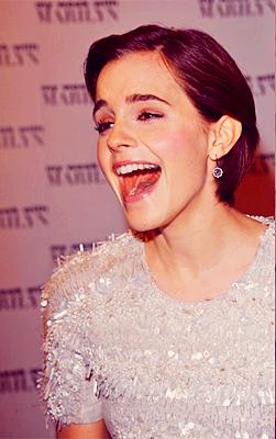 actriz emma watson riendo usando un vestido de color perla con brillos