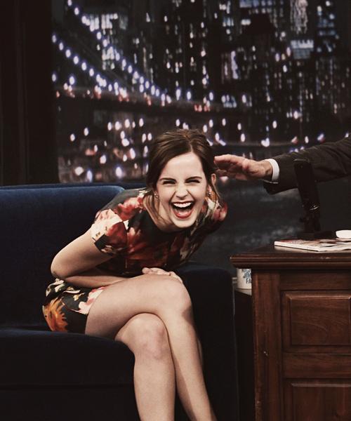 emma watson sonriendo mientras esta sentada en un sillón y le dan una palmada en el hombro