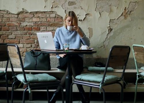 mujer sentada tomando café y revisando su computadora
