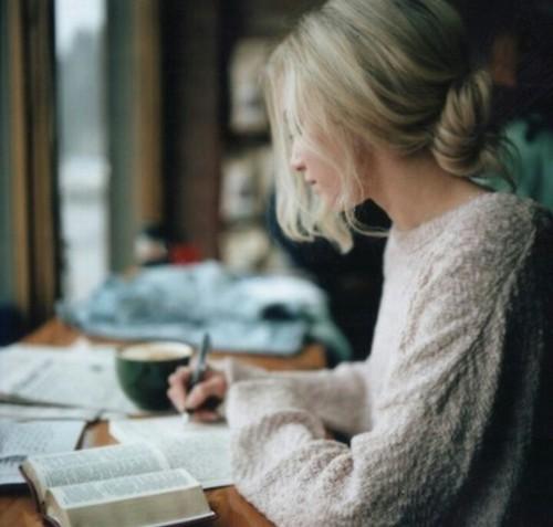 mujer con libros en una mesa escribiendo en una libreta