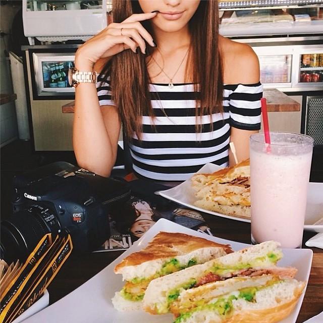 mujer sentada frente a comida decidiendo que comer
