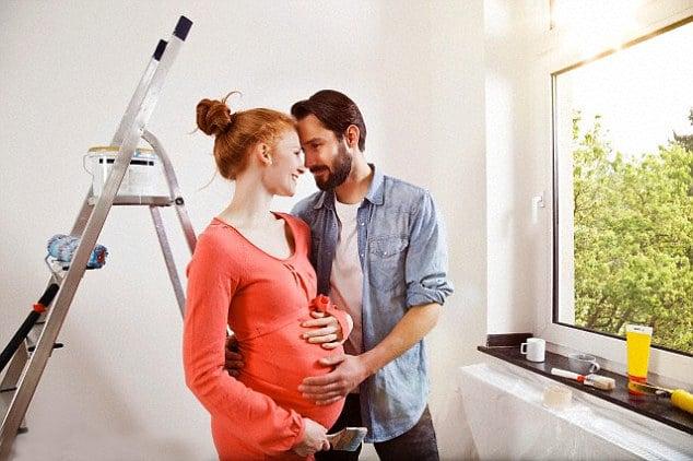 mujer embarazada y hombre en medio de una habitación pintando