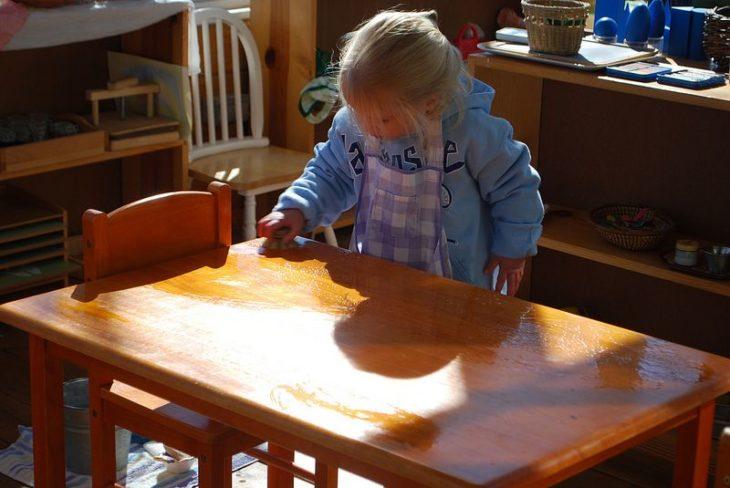 Niña pequeña limpiando una mesa