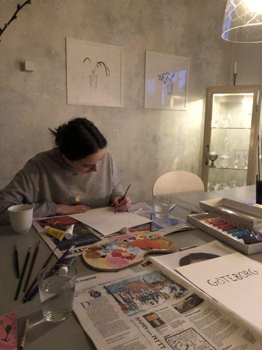 chica trabajando en planos de arquitectura sobre un restirador