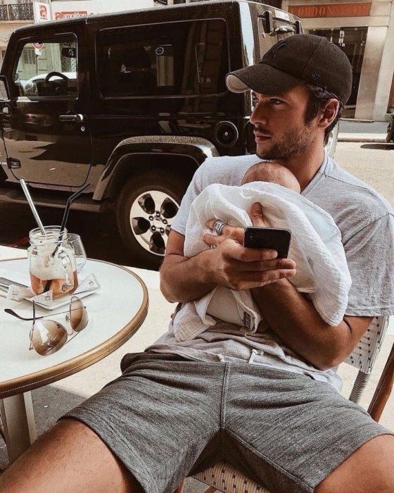 Papá joven con bebé en brazos y con celular en mano