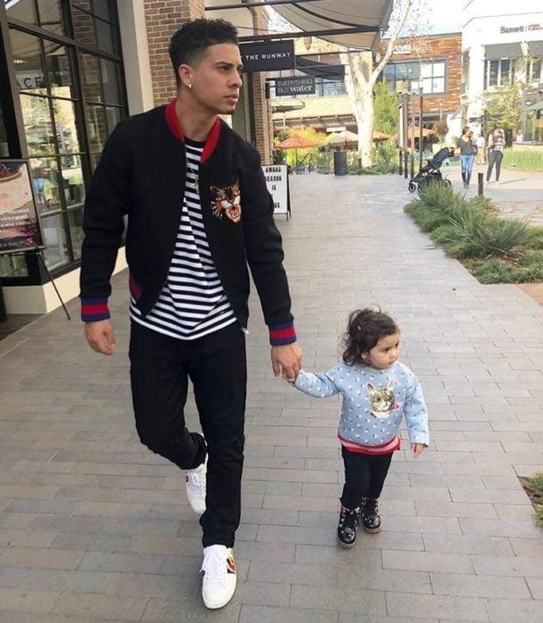 Papá joven paseando con su hijita de la mano