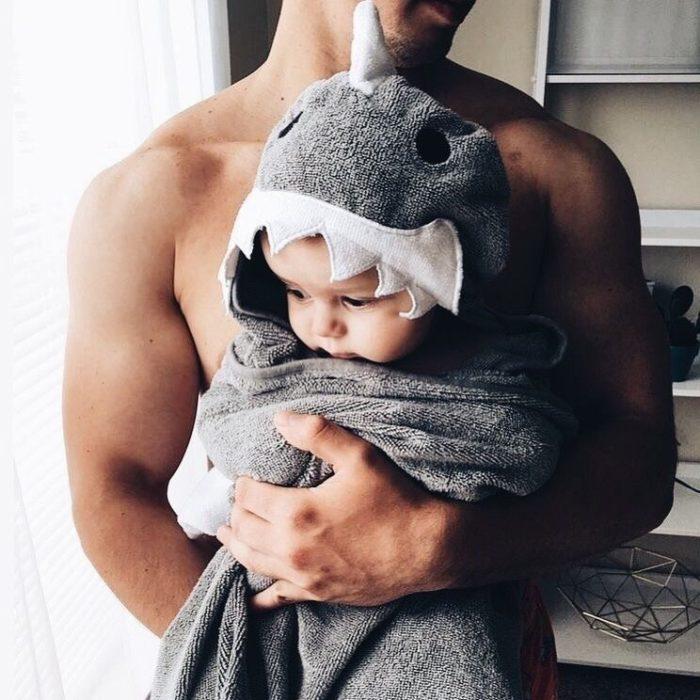 Papá con bebé en brazos envuelta en una toalla de tiburón