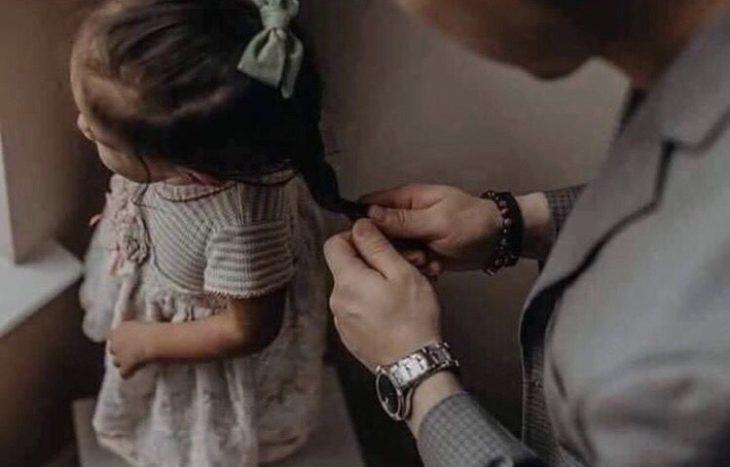 papá haciendo trenzas a su hija pequeña