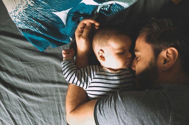 Papá durmiendo a su hijo bebé
