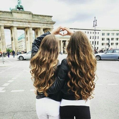 dos chicas en la calle formando un corazón con ambas manos