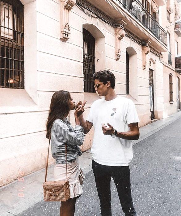 Pareja de novios comiendo algo en la calle