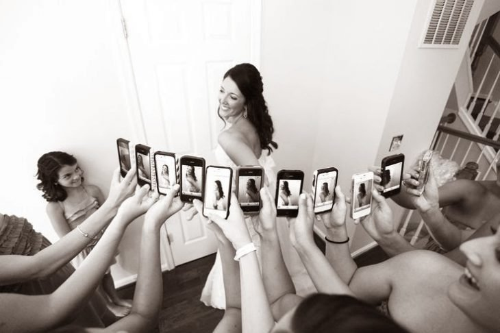 novia siendo fotografiada por muchos celulares
