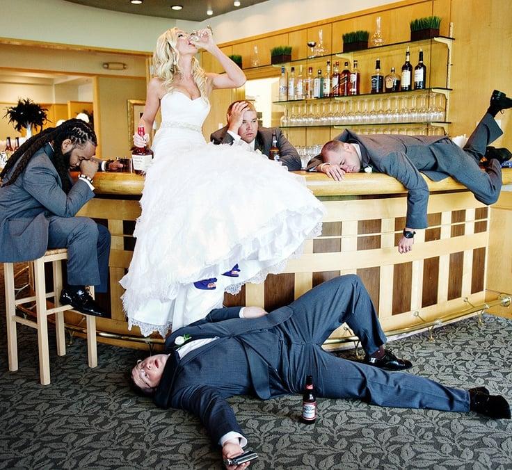 mujer vestida de novia bebiendo alcohol sentada en una barra rodeada de hombres