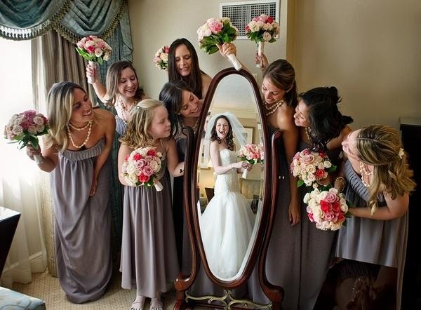 damas de honor rodeando un espejo donde se refleja la novia