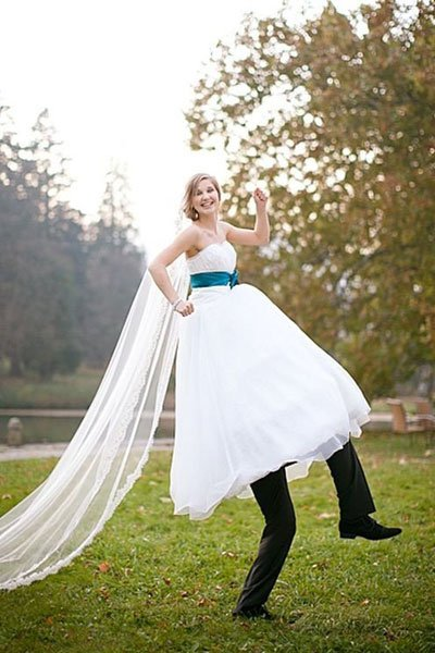 novio cargando a una mujer vestida de novia simulando que son zancos