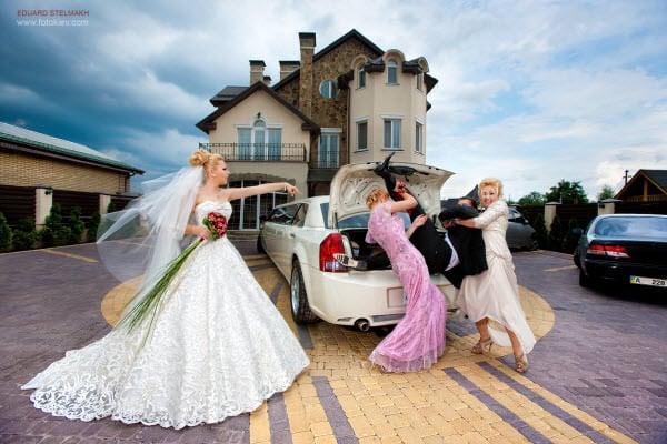 novia ordenando que suban al novio en el maletero de un carro