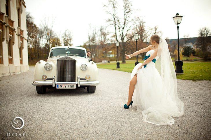mujer vestida de novia levantandose el vestido mientras espera que un hombre la recoja en un carro