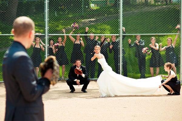 mujer vestida de novia esperando para batear una pelota de béisbol lanzada por un hombre