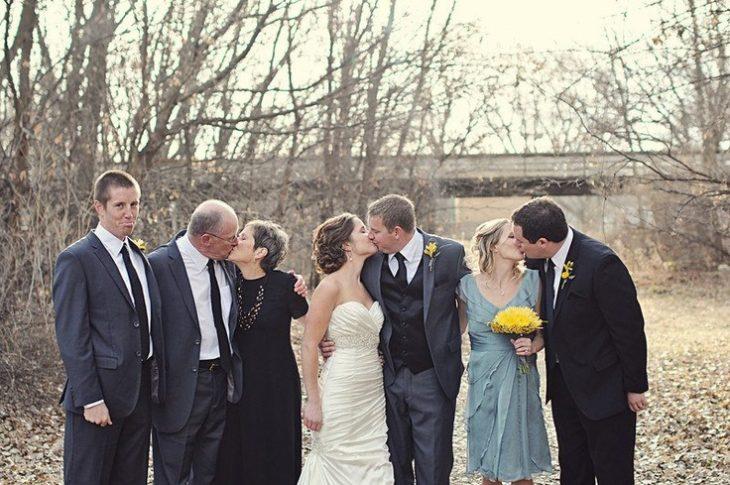parejas besandose y una persona sin pareja parados en un jardín