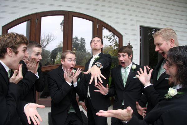 hombre enseñando el anillo de bodas a sus amigos mientras lo ven sorprendidos