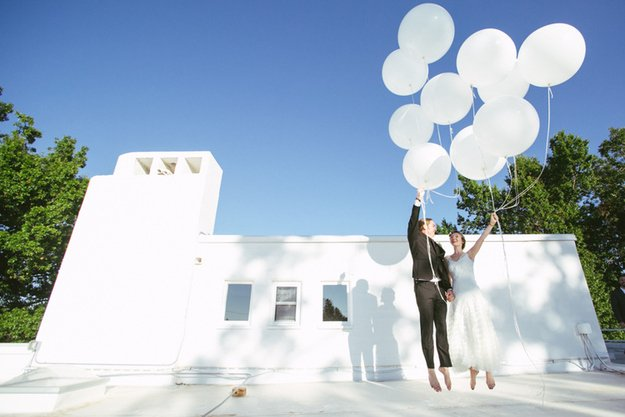 novios frente a una casa sujetando globos blancos