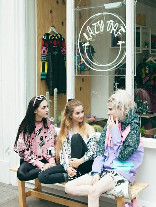 amigas sentadas hablando afuera de una tienda