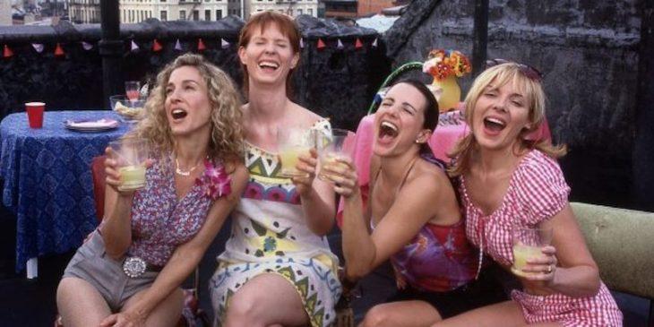 mujeres ríendose mientras están sentadas bebiendo