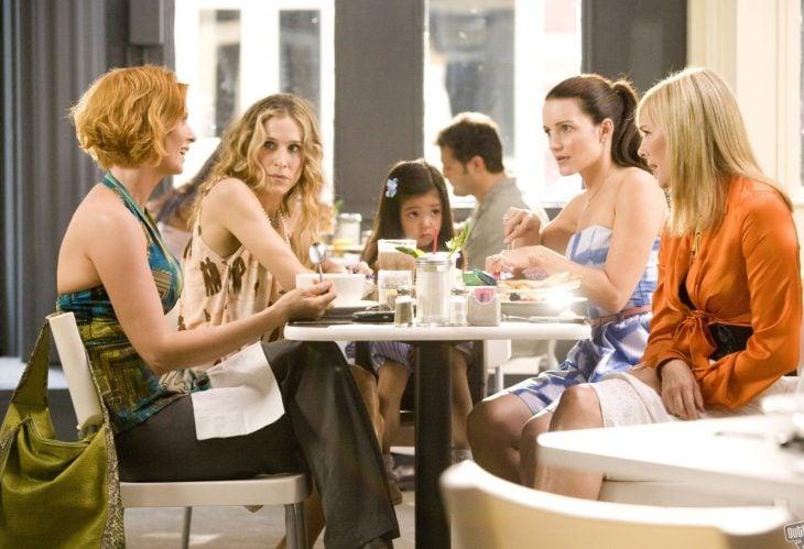 mujeres sentadas en la mesa comiendo y platicando