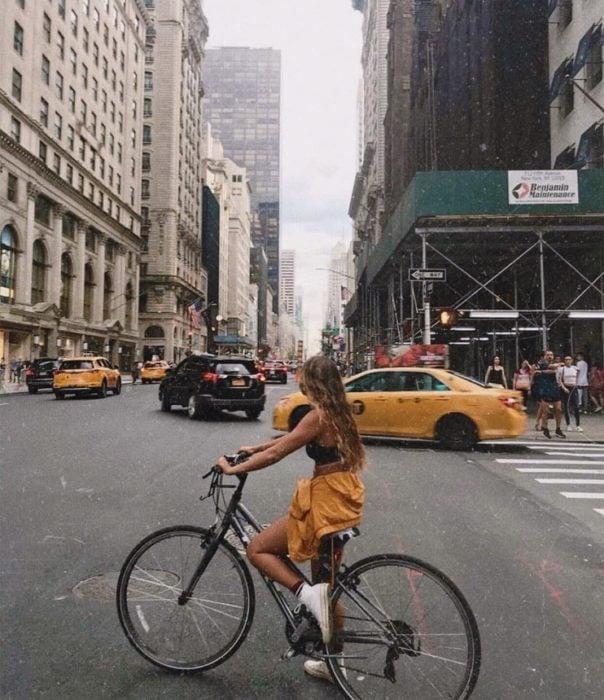 Chica con cabello largo paseando en la calle en una bicicleta