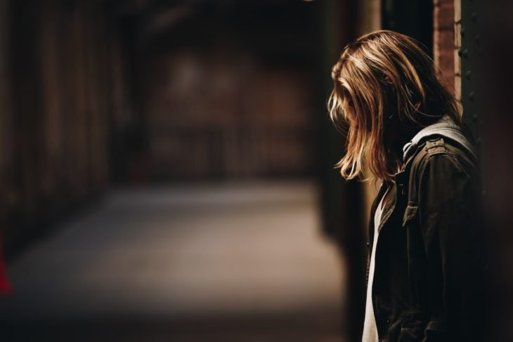 Chica recargada en la pared con un pasillo largo al fondo