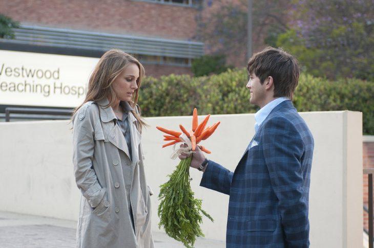 hombre sosteniendo un ramo de zanahoras en las manos para entregárselo a una mujer