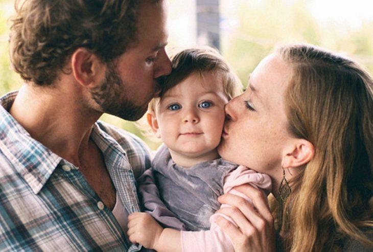 Foto de niña pequeña con sus dos padres