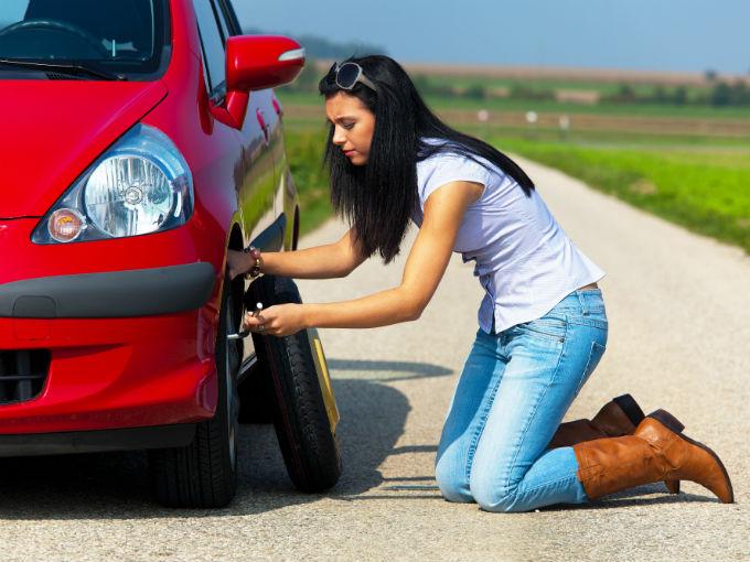 mujer agachada cambiando una llanta de un automóvil de color rojo
