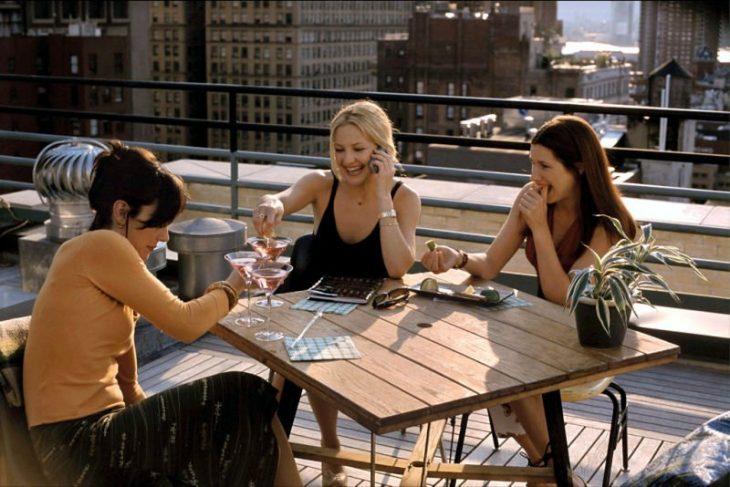 mujeres reunidas y sentadas en una mesa brindando con una copa de vino