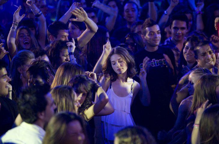mujer bailando en un antro con gente al rededor